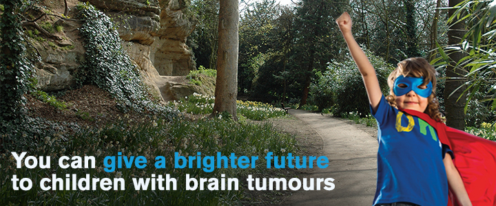 A young boy dressed as a superhero stands in front of the woodland path. Caption: You can give a brighter future to children with brain tumours.