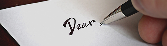 A hand starting to write a letter
